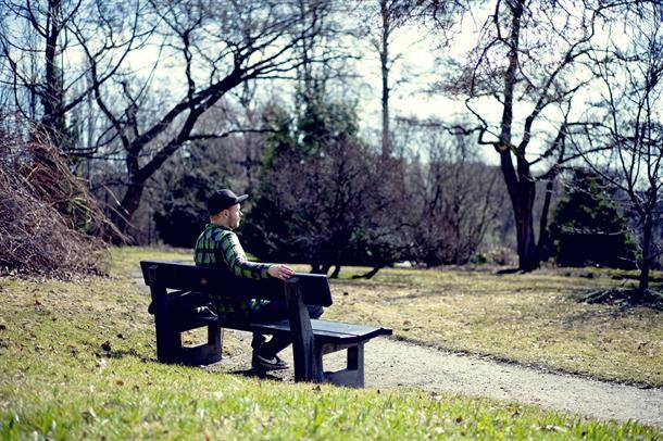 Ung mann sitter alene på en benk ute i naturen.
