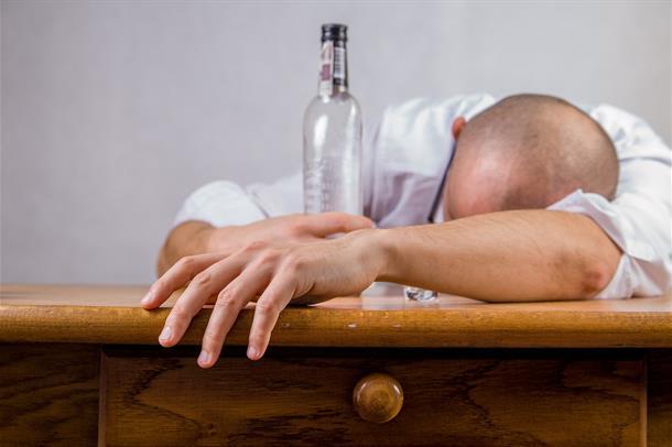 Mann som ligger over et bord. Med en flaske i hånden