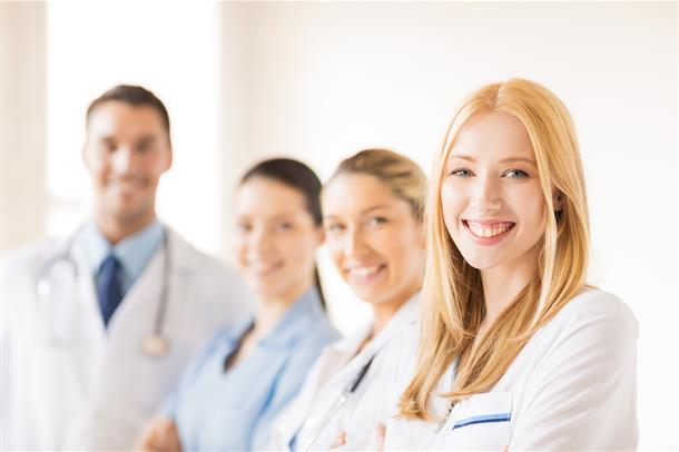 Fire smilende sykepleierstudenter. Tre damer og en mann.