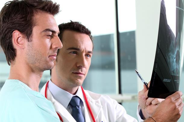 To mannlige leger ser på et røntgenbilde sammen.