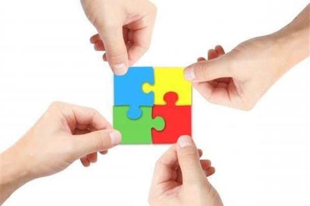 Fire hender som holder hver sin puzlespillbrikke. Brikkene er puzlet sammen til en firkant.