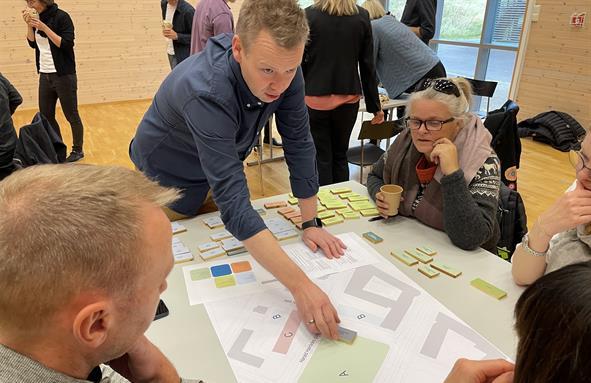 Vegard Vestvik legger byggeklosser på bordet,, lager minimodell av senter for psykisk helse sammen med flere andre i gruppa.