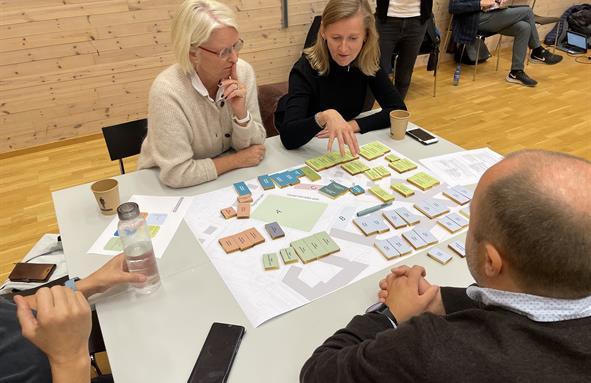 Det legges byggeklosser av psykisk helse på bordet, og deltakerne diskuterer hvordan de skal bygge.